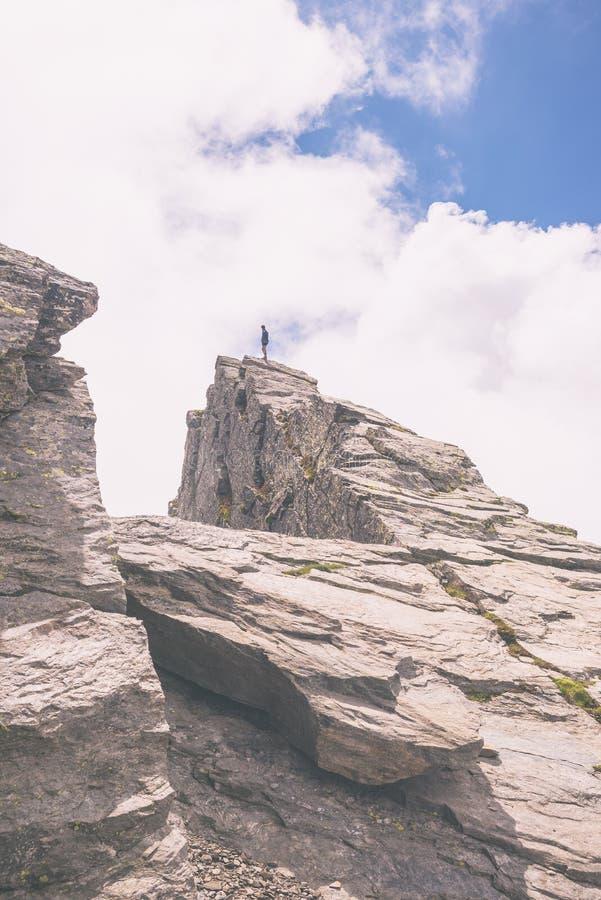 站立在山峰,被定调子的图象的远足者 免版税库存图片