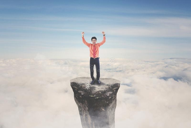 站立在山的成功的男性企业家 免版税图库摄影