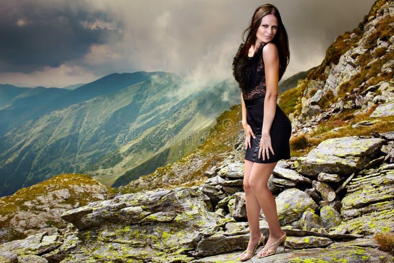 站立在山的礼服的典雅的夫人晃动 图库摄影