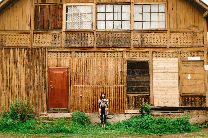 站立在山的老木房子的时髦的行家妇女