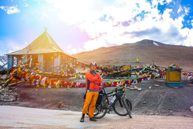 站立在山路,查谟和克什米尔状态,北部印度的年轻自行车骑士 库存图片