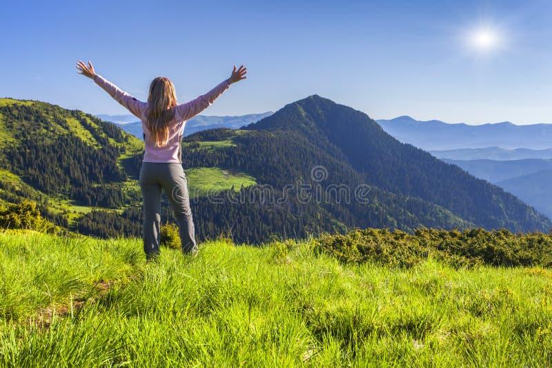 站立在山顶部和享受一个早晨的年轻远足者 库存图片