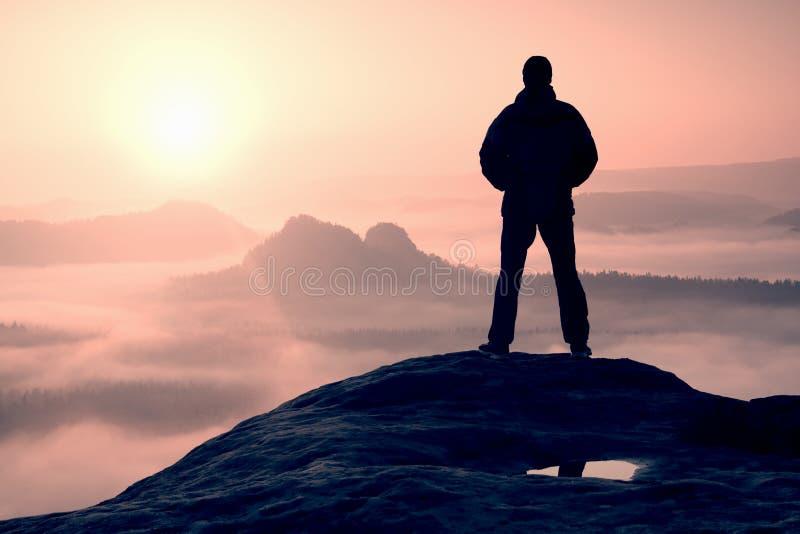 站立在山顶部和享受日出的单独远足者 库存照片