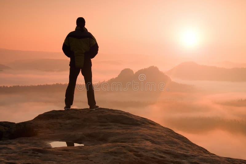 站立在山顶部和享受日出的单独远足者 免版税图库摄影