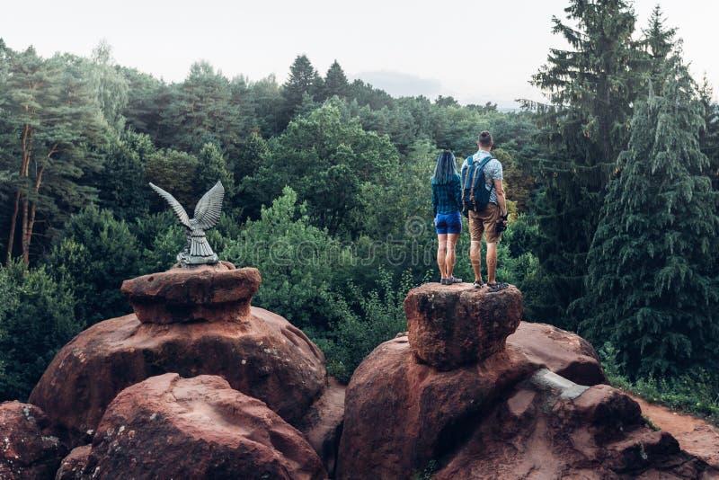 站立在山顶部和享受自然的看法背包徒步旅行者年轻夫妇在夏天 库存图片
