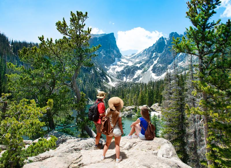 站立在山顶部的家庭享受美好的风景 免版税库存照片