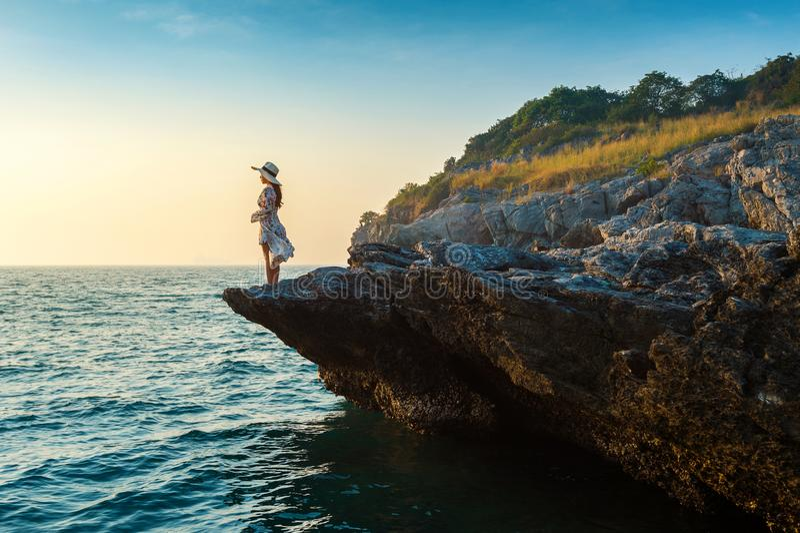 站立在岩石上面和看海滨和日落的少妇在Si张海岛 库存图片