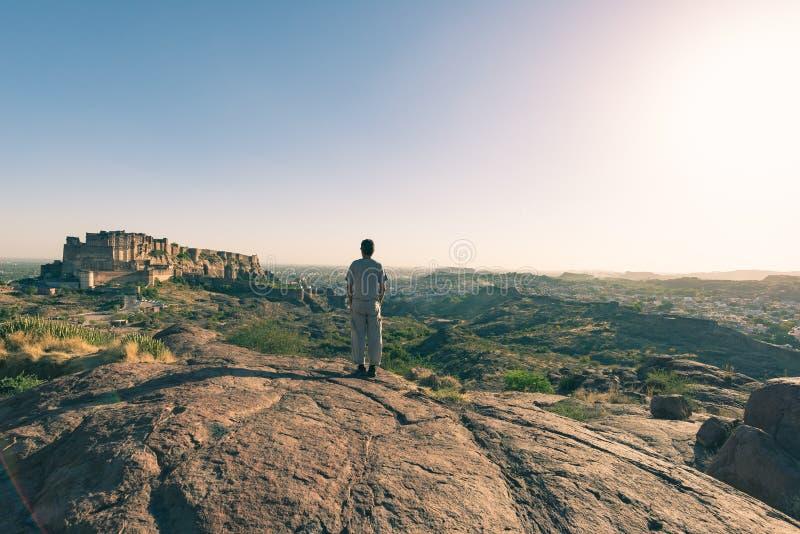 站立在岩石和从上面看乔德普尔城堡垒的膨胀的看法游人,栖息在控制蓝色镇的上面 旅行 库存照片