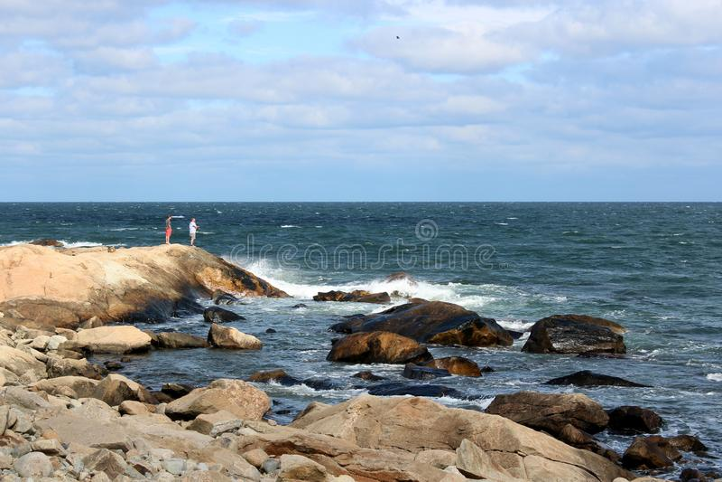 站立在岩石岸的人们,享受一海滩天,Narragansett,罗德岛,2018年 库存照片