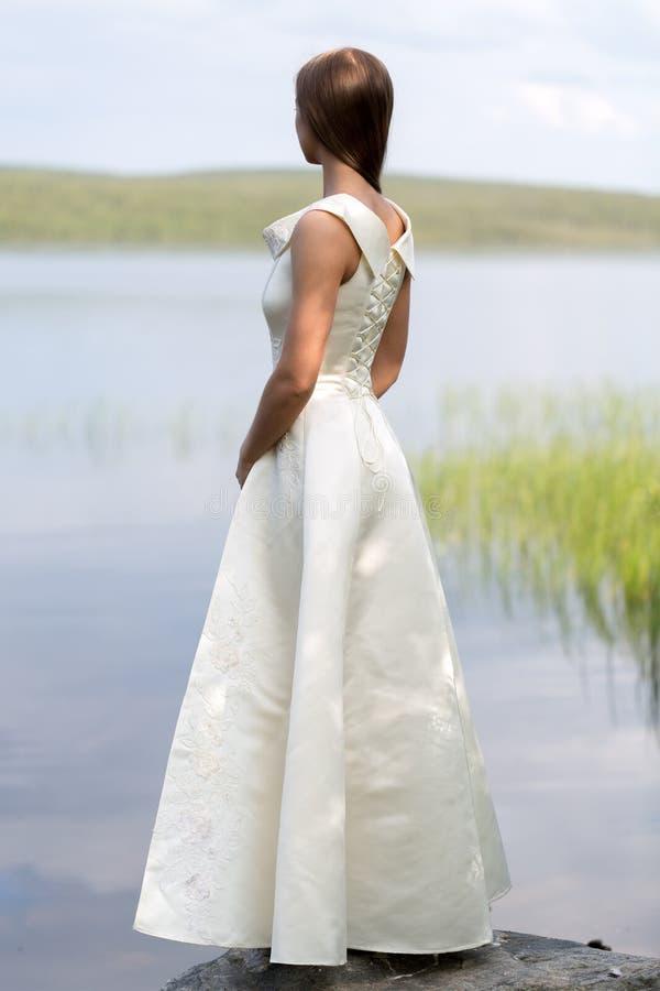 站立在岩石的一件白色礼服的女孩 免版税图库摄影