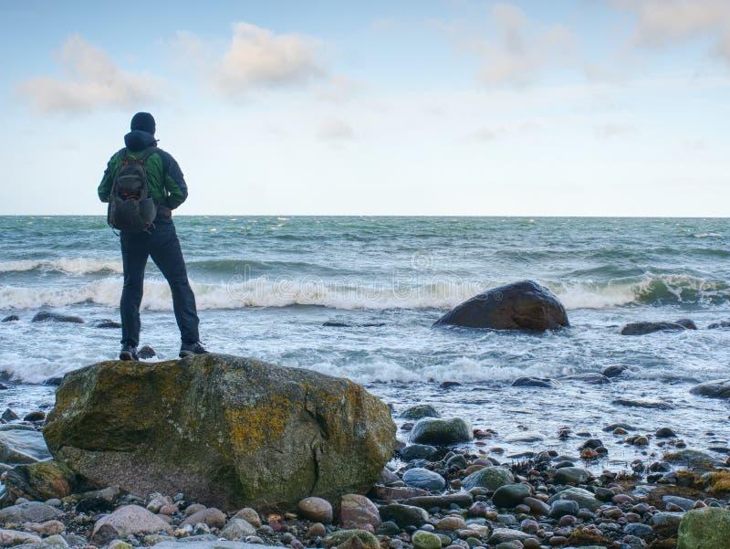 站立在岩石的人在海洋中间 单独旅游立场 库存照片