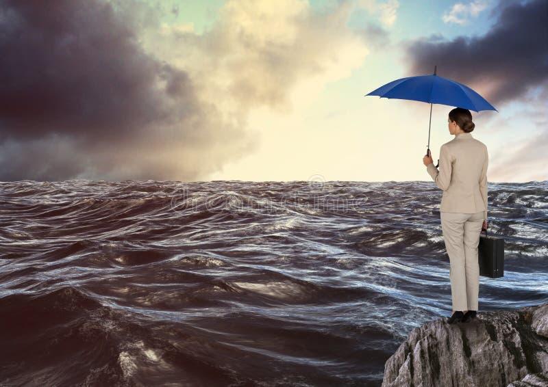 站立在岩石的女实业家背面图拿着蓝色再看海的伞和公文包 免版税库存照片