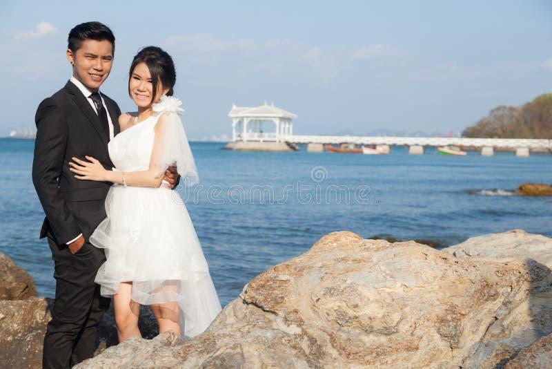 站立在岩石的新娘和新郎 免版税库存图片