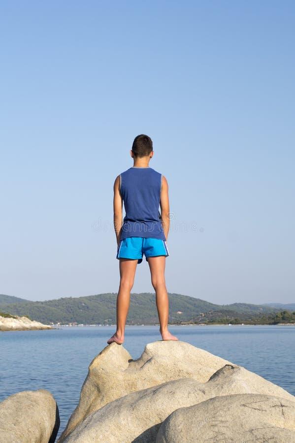 站立在岩石的男孩在海旁边 库存照片