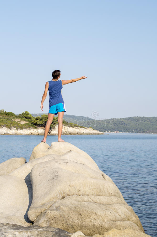 站立在岩石的男孩在海旁边 库存图片