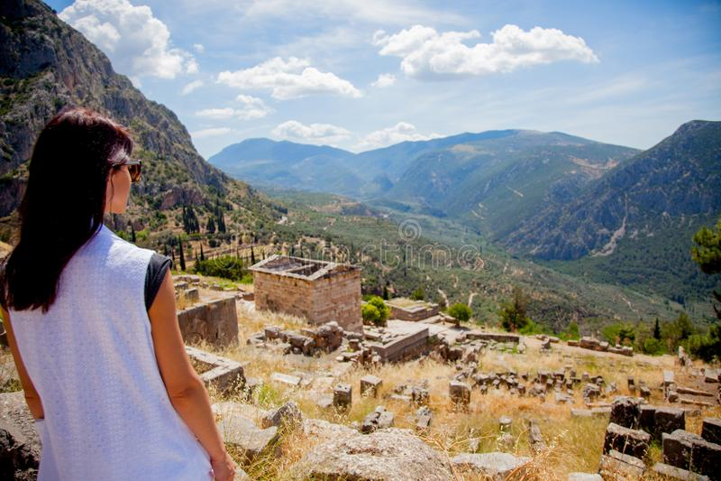 站立在岩石的白色衣裳的女孩在希腊 免版税库存图片