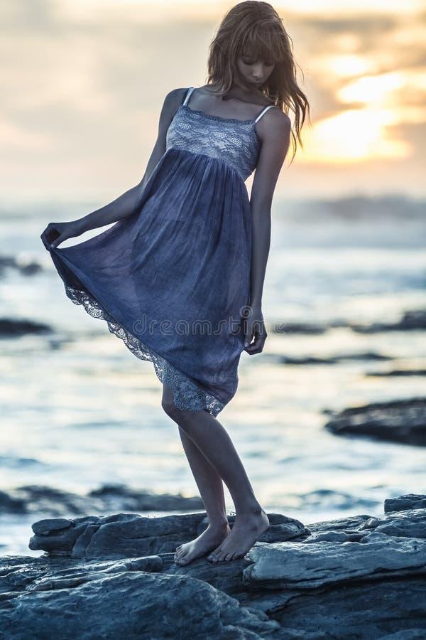 站立在岩石的美丽的少妇在海旁边 免版税库存照片