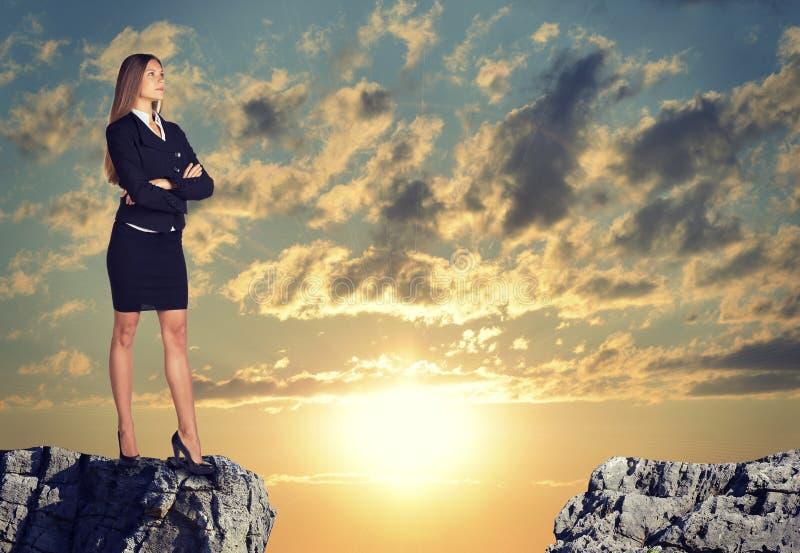 站立在岩石空白边缘的女实业家 库存照片