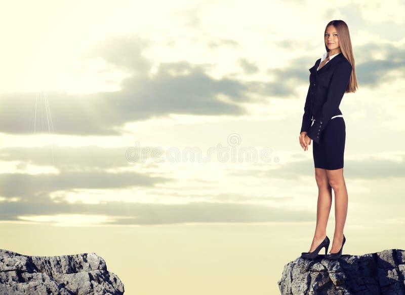 站立在岩石空白边缘的女实业家 免版税库存图片