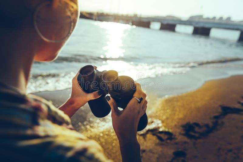 站立在岸和拿着双筒望远镜的无法认出的女孩 侦察员旅行癖旅行概念 免版税库存图片