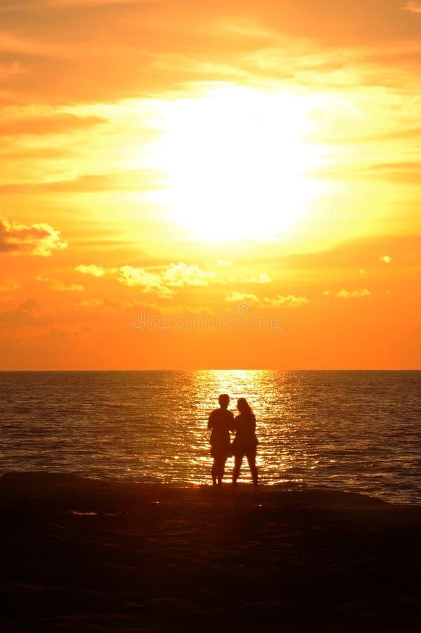 站立在岸和神色的年轻夫妇在落日 库存图片