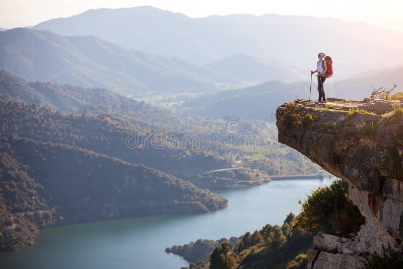 站立在峭壁的女性远足者 库存图片