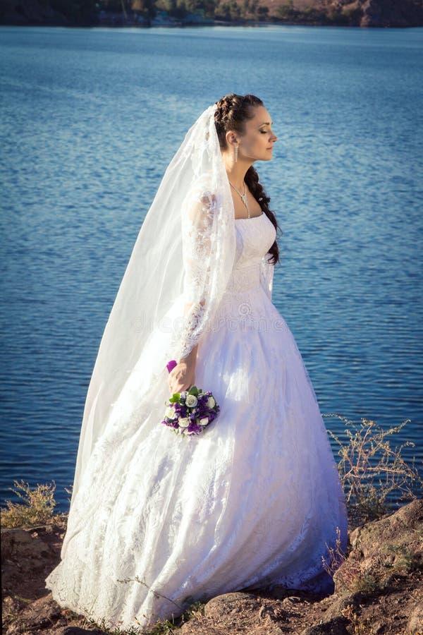 站立在峭壁的新娘 免版税图库摄影