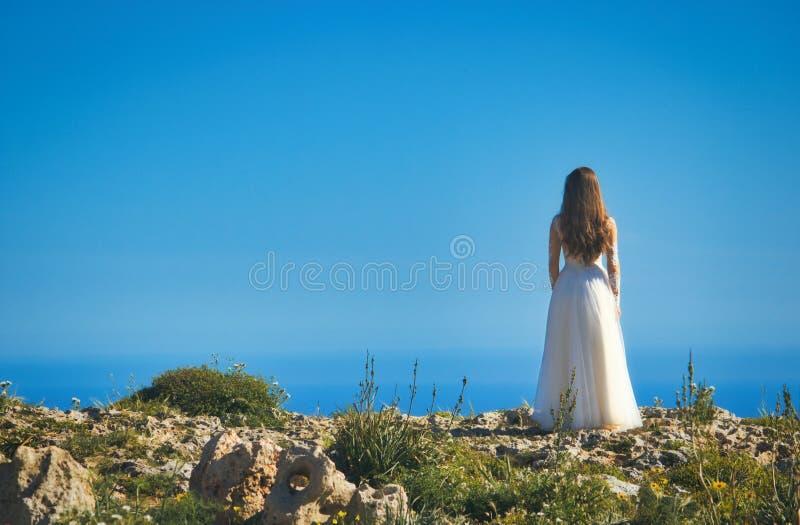 站立在峭壁边缘的一白色婚纱的一个新娘看对海 图库摄影