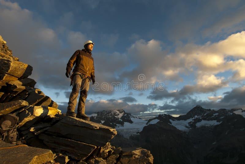 站立在峭壁边缘的年轻登山人 免版税库存照片