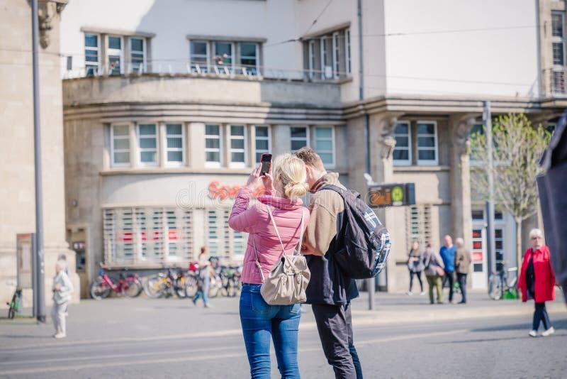 埃福特,德国 2019?4?7? 站立在市中心的夫妇 做图片的妇女 库存照片