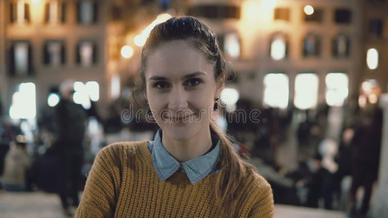 站立在市中心的年轻美丽的妇女画象在晚上 学生女孩看照相机,微笑 图库摄影