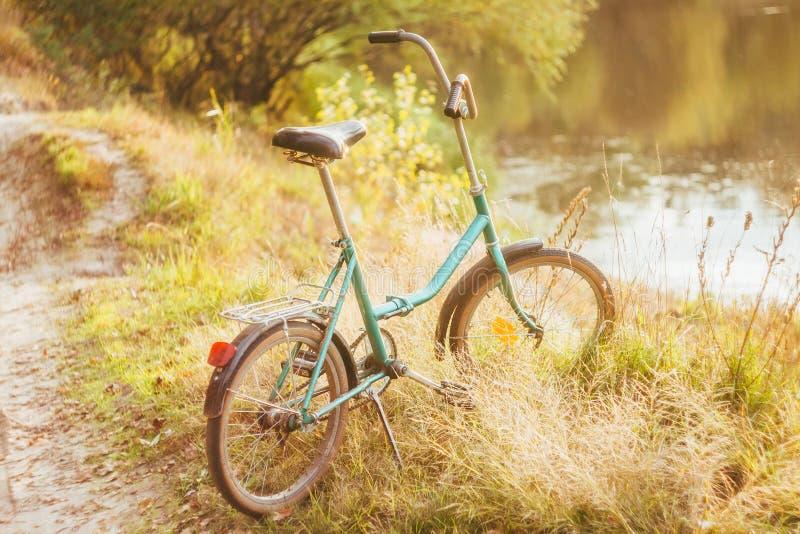 站立在干燥黄色草的绿色夏天或秋天草甸的绿色自行车 库存照片