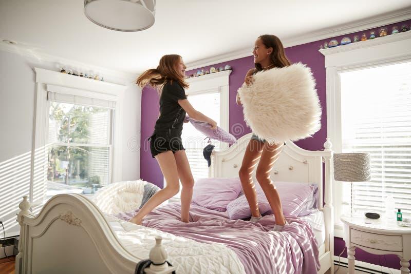 站立在床上的两个十几岁的女孩有枕头战 免版税图库摄影