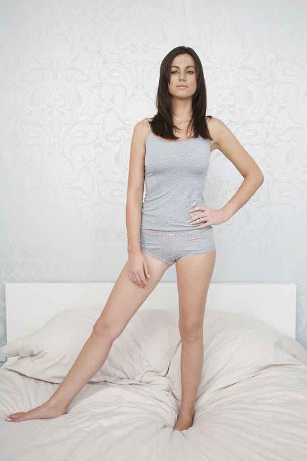 站立在床上的睡衣的确信的妇女 库存图片