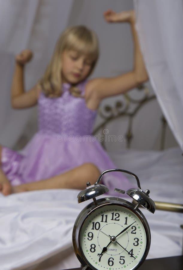 站立在床头柜上的闹钟 醒一个睡着的女孩舒展在床上在背景中 图库摄影