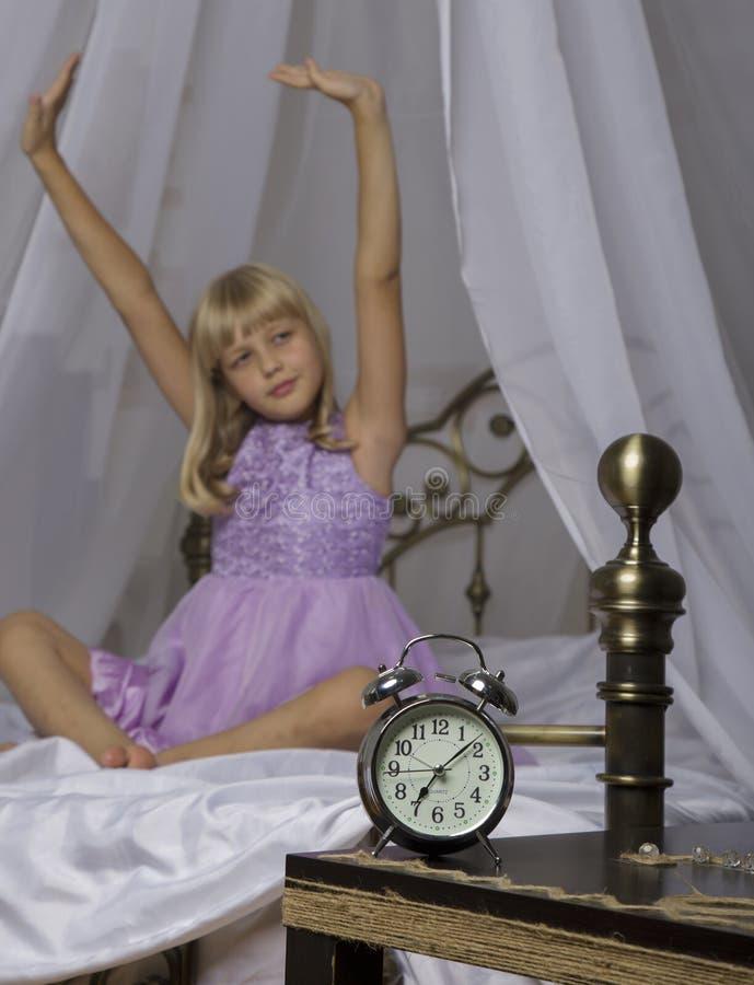站立在床头柜上的闹钟 醒一个睡着的女孩舒展在床上在背景中 库存图片