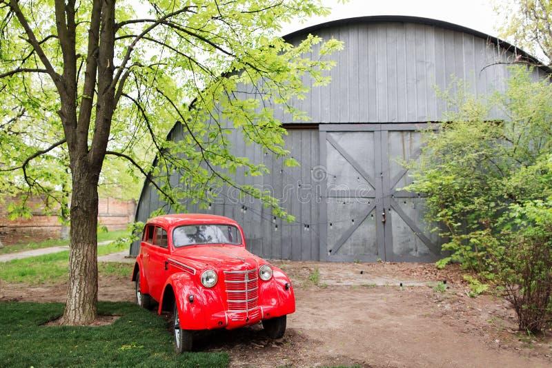 站立在庭院里的红色减速火箭的小葡萄酒汽车在夏天 库存照片