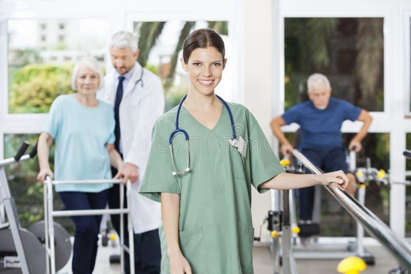 站立在康复中心的确信的女性生理治疗师 库存图片