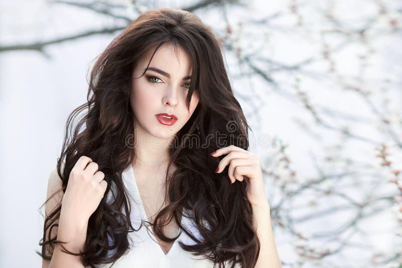 站立在开花的树的美丽的女孩在白色背景的庭院里 免版税库存图片