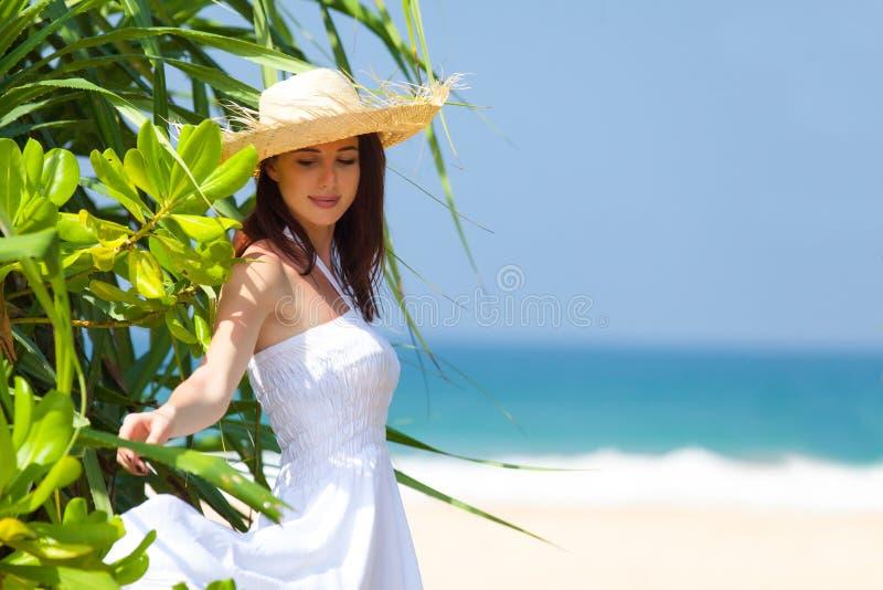 站立在异乎寻常的树附近和微笑在t的美丽的少妇 免版税图库摄影
