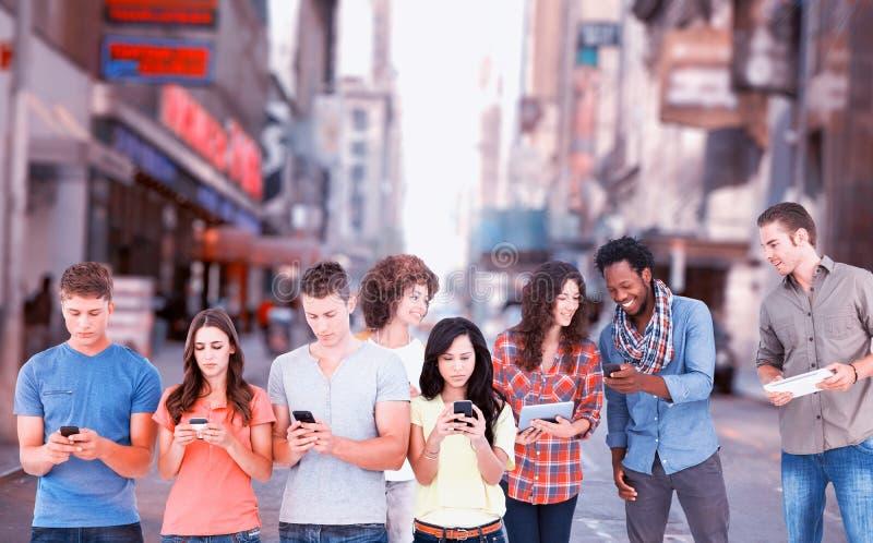站立在彼此旁边和发短信在他们的电话的四个人的综合图象 库存照片