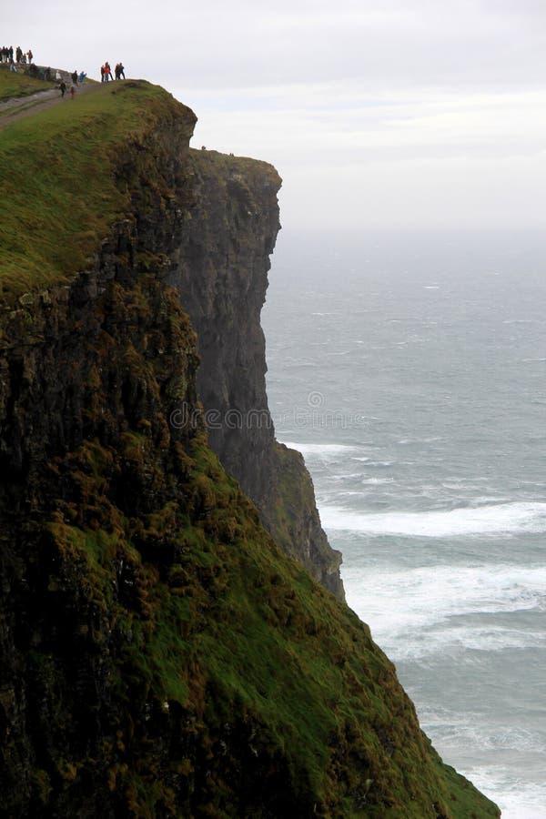 站立在悬崖,峭壁Moher,大西洋海岸,爱尔兰, 2014年10月边缘的Vistors  图库摄影