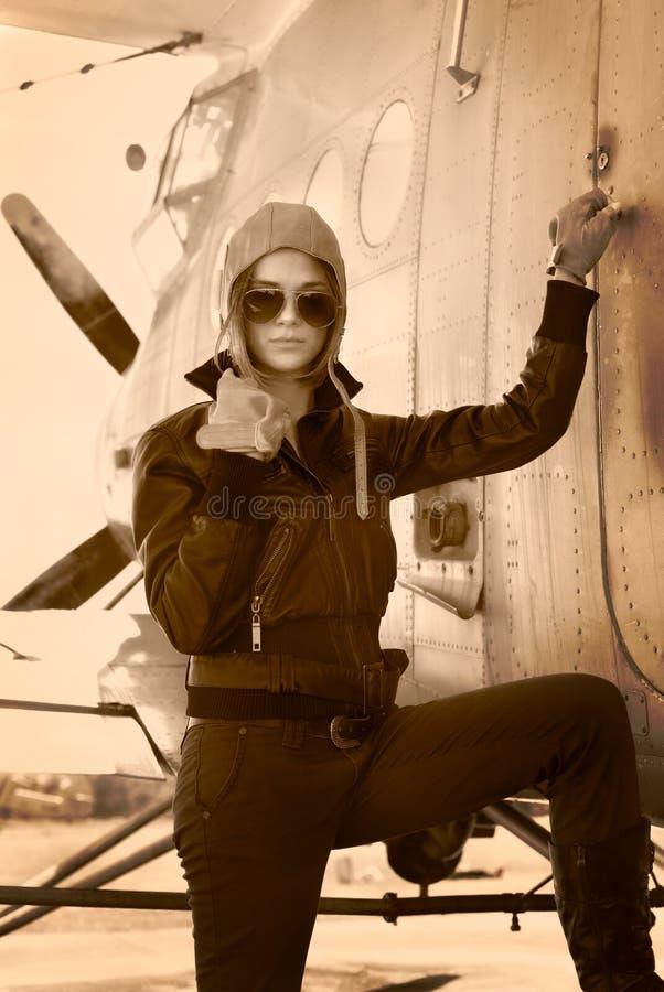 站立在战争航空器旁边的夹克的美丽的女孩。 免版税库存图片