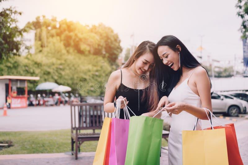 站立在户外与神色的商城的亚裔妇女朋友 免版税库存图片