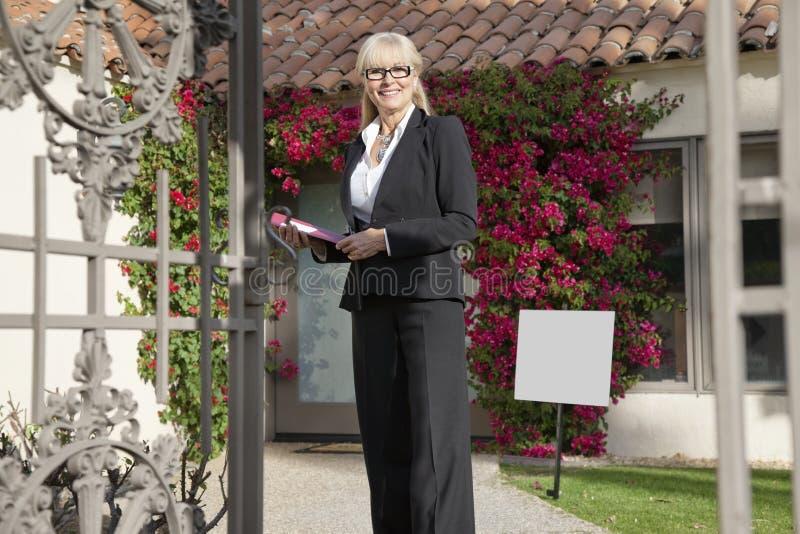 站立在房子前面的一名愉快的资深房地产开发商的画象 免版税库存照片