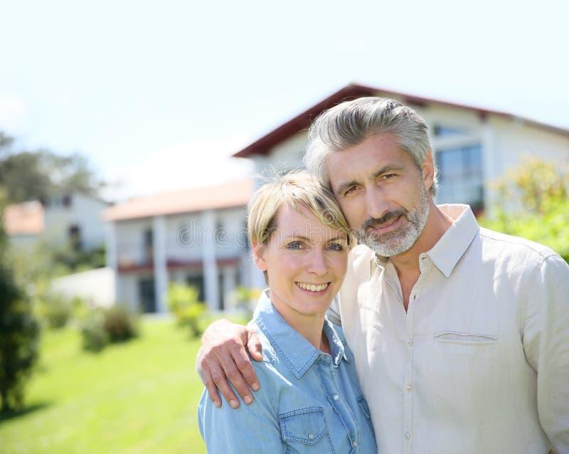 站立在房子的前面的利德尔年迈的夫妇 免版税库存图片