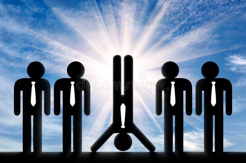 站立在手上的人在站起来的普通人中引人注意 免版税库存图片