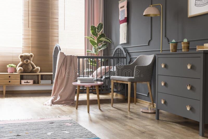 站立在扶手椅子、灯和cupbo旁边的轻便小床的真正的照片 库存照片