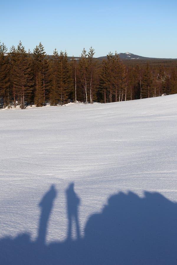 站立在拉普兰风景的小山的两人的阴影在冬天 库存图片