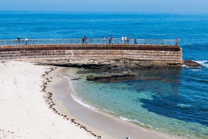 站立在拉霍亚儿童` s水池防波堤上的访客 免版税库存图片